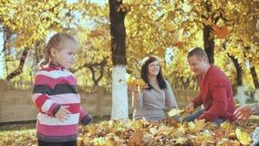 Szczęśliwa rodzina outdoors bawić się z spadać liśćmi w pogodnej jesieni pogodzie Rodzica buziak w tle zbiory