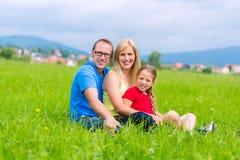 Szczęśliwa rodzina outdoors siedzi na trawie Fotografia Stock