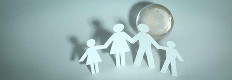 Szczęśliwa rodzina papierowi mężczyzna stoi blisko szklanej kuli ziemskiej Obraz Stock