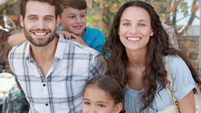 Szczęśliwa rodzina patrzeje kamerę w zakupy centrum handlowym