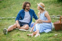 Szczęśliwa rodzina picnicking outdoors z ich śliczną córką, błękitów ubrania, kobieta w kapeluszu fotografia royalty free