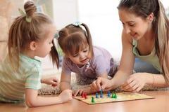 szczęśliwa rodzina Potomstwa matkują bawić się Ludo boardgame z jej córkami podczas gdy wydający czas wpólnie w domu obraz stock