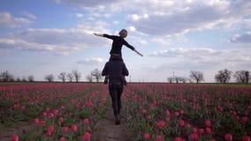 Szczęśliwa rodzina, potomstwa ojcuje z dzieckiem chłopiec na ramionach robi płaskim rękom bawić się łąkę tulipany w kwiaty zbiory