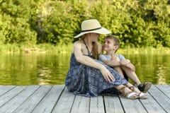 Szczęśliwa rodzina, potomstwo matka z jej małym synem siedzi na molu rzeką zdjęcia royalty free