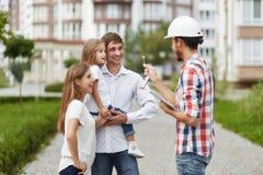 Szczęśliwa rodzina przed nowym budynkiem mieszkaniowym Fotografia Royalty Free