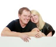 Szczęśliwa rodzina przy białym sztandarem Zdjęcia Stock