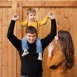 Szczęśliwa rodzina przy drewnianą ścianą obraz stock