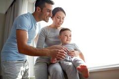 Szczęśliwa rodzina przy okno Zdjęcie Stock