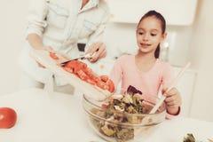 Szczęśliwa rodzina Przygotowywa sałatki Przy kuchnią obraz royalty free