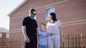 Szczęśliwa rodzina stoi przed domem trzy Mama, tata i chłopiec, zdjęcie wideo