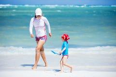 Szczęśliwa rodzina trzy bawić się na plaży, stawia ich ręki na górze each inny zdjęcia royalty free