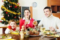 Szczęśliwa rodzina trzy ma Bożenarodzeniowego gościa restauracji Zdjęcie Royalty Free