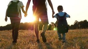 Szczęśliwa rodzina turyści: Tata i jego dwa syna chodzimy naturą z plecakami w zmierzchu Pojęcie zbiory wideo
