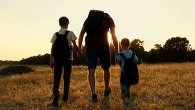 Szczęśliwa rodzina turyści: Tata i jego dwa syna chodzimy naturą z plecakami w zmierzchu Pojęcie zdjęcie wideo