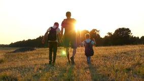 Szczęśliwa rodzina turyści: Tata i jego dwa syna chodzimy w naturze z plecakami Pojęcie turystyka i zbiory