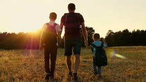 Szczęśliwa rodzina turyści w naturze: Tata i jego dwa syna iść z plecakami przy zmierzchem Pojęcie turystyka i zbiory wideo