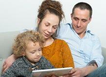 Szczęśliwa rodzina używa pastylkę obraz royalty free