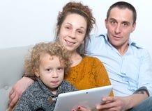 Szczęśliwa rodzina używa pastylkę zdjęcia royalty free