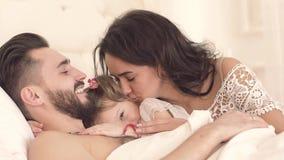 Szczęśliwa rodzina w łóżku budzi się up ślicznej małej córki zdjęcie wideo