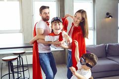 Szczęśliwa rodzina w bohaterów kostiumach bawić się wpólnie obraz royalty free