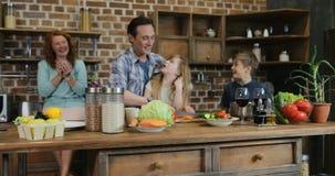 Szczęśliwa rodzina w kuchennym narządzania jedzeniu, macierzystym patrzeje ojcu i dzieciach gotuje wpólnie w domu, zdjęcie wideo