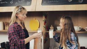 Szczęśliwa rodzina w kuchni Mama i córka pijemy świeżego mleko i uśmiech Wapnie, śniadanie, zdrowy Zwolnione tempo zbiory