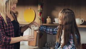 Szczęśliwa rodzina w kuchni Mama nalewa mleko w szkło dla jej córki Wapnie, śniadanie, zdrowy Zwolnione tempo zbiory wideo