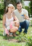 Szczęśliwa rodzina w ogródzie z ogrodniczy rozmaitym zdjęcia royalty free