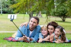 Szczęśliwa rodzina w parkowym bierze selfie zdjęcie royalty free