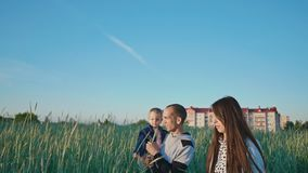 Szczęśliwa rodzina w pszenicznym polu wśród zielonych spikelets Ojciec utrzymuje córki w ona ręki Wpólnie joyfully podnosi ich zbiory wideo