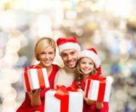 Szczęśliwa rodzina w Santa pomagiera kapeluszach z prezentów pudełkami Zdjęcia Royalty Free