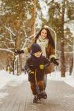 Szczęśliwa rodzina w zimy odzieży Uśmiechnięty syn biega zdala od jego matki plenerowej Zdjęcie Stock