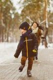 Szczęśliwa rodzina w zimy odzieży Uśmiechnięty syn biega zdala od jego matki plenerowej Obrazy Royalty Free