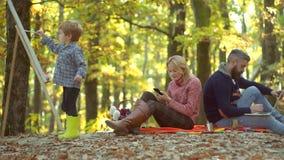 Szczęśliwa rodzina wpólnie w żółtej naturze Szczęśliwi uśmiechnięci potomstwa wychowywają z małym synem kłaść w jesień liściach s zdjęcie wideo