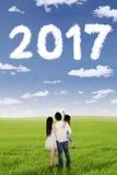 Szczęśliwa rodzina wskazuje chmura kształtującą liczbę 2017 Fotografia Royalty Free