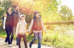 Szczęśliwa rodzina wycieczkuje w drewnach z plecakami fotografia royalty free