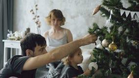 Szczęśliwa rodzina z śliczną małą córką przygotowywa otwierać prezentów pudełka blisko choinki w domu zdjęcie wideo