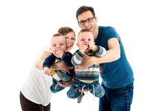 Szczęśliwa rodzina z adoptowanymi bliźniakami jest roześmiana Na biel Fotografia Stock