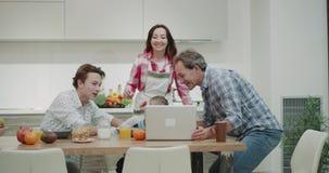 Szczęśliwa rodzina z dojrzałymi rodzicami wydaje ładnego śniadanie wpólnie podczas gdy mama kulinarny tata pokazuje ładnego wideo zbiory wideo