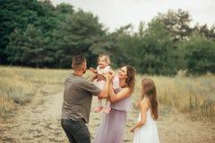 Szczęśliwa rodzina z dwa dziećmi zabawę i śmia się na spacerze fotografia royalty free