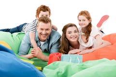 szczęśliwa rodzina z dwa dzieciakami kłama na bobowej torby krzesłach i ono uśmiecha się przy kamerą po robić zakupy zdjęcie stock