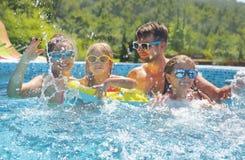 Szczęśliwa rodzina z dwa dzieciakami ma zabawę w pływackim basenie obrazy royalty free