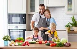 Szczęśliwa rodzina z dziećmi przygotowywa jarzynowej sałatki Obrazy Royalty Free