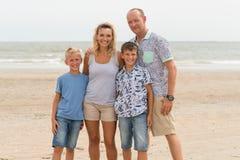 Szczęśliwa rodzina z dziećmi stoi na pogodnej plaży Zdjęcie Stock