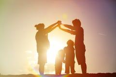 Szczęśliwa rodzina z dzieciakami i ciężarną matką przy zmierzchem wpólnie Obraz Royalty Free