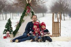 Szczęśliwa rodzina z dzieciakami, mieć zabawę plenerową w śniegu na Chrystus obrazy royalty free