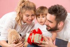 Szczęśliwa rodzina z dzieciakiem wpólnie i ono uśmiecha się przy kamerą odizolowywającą na menchiach obrazy stock