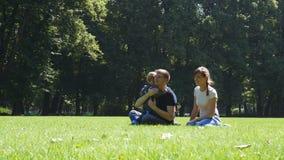 Szczęśliwa rodzina z dziecka obsiadaniem na trawie w lato parku zbiory