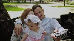 Szczęśliwa rodzina z dzieckiem bierze selfie na ławce w parku zbiory