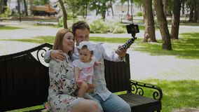 Szczęśliwa rodzina z dzieckiem bierze selfie na ławce w parku zbiory wideo